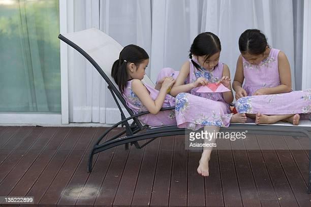 Three girls making paper boats
