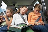 Three girls (6-8 years) on rear car seat, close-up