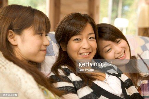 Three girls on the sofa, smiling : Stock Photo