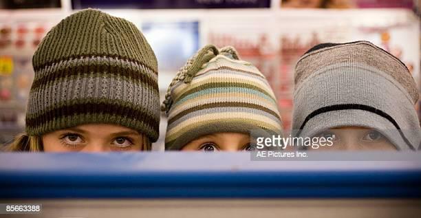 Three girls peek over store shelf