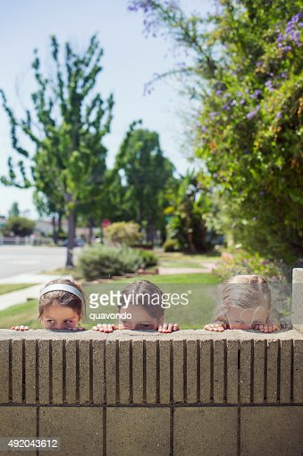 Three girls peeping over a wall