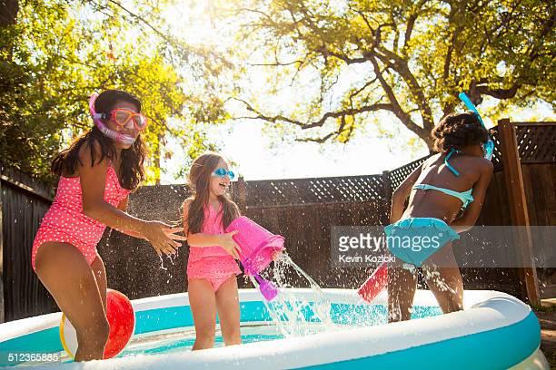 Three girls playing and splashing in garden paddling pool