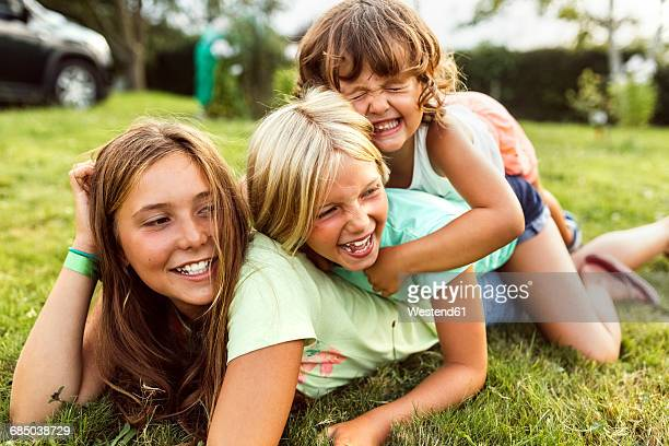 Three girls playing together on a meadow
