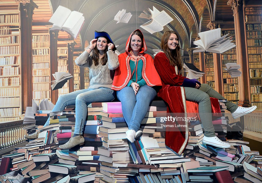 Three girls pose for a photo in front of photowall with motiv of a phantasy library at the 2013 Frankfurt Book Fair on October 9, 2013 in Frankfurt, Germany. This year's fair will be open to the public from October 9-13 and the official partner nation is Brazil.