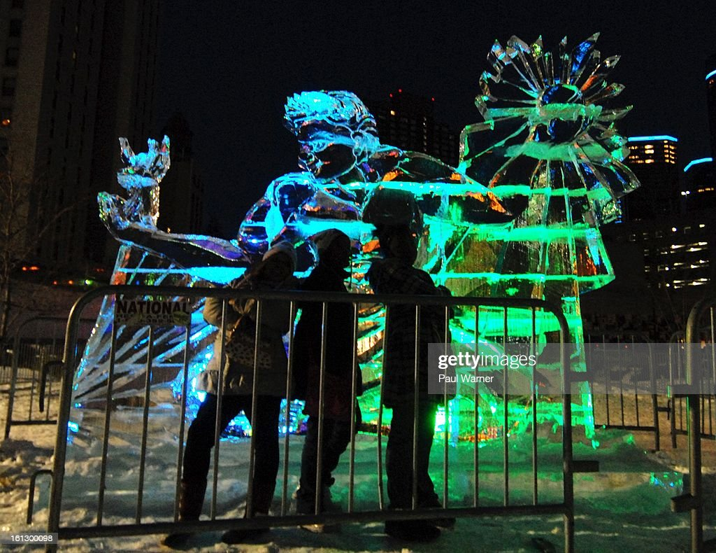 Three girls pose for a picture in front of a ice sculpture of the Spirit of Detroit statue at Motown Winter Blast at Campus Martius Park on February 9, 2013 in Detroit, Michigan.