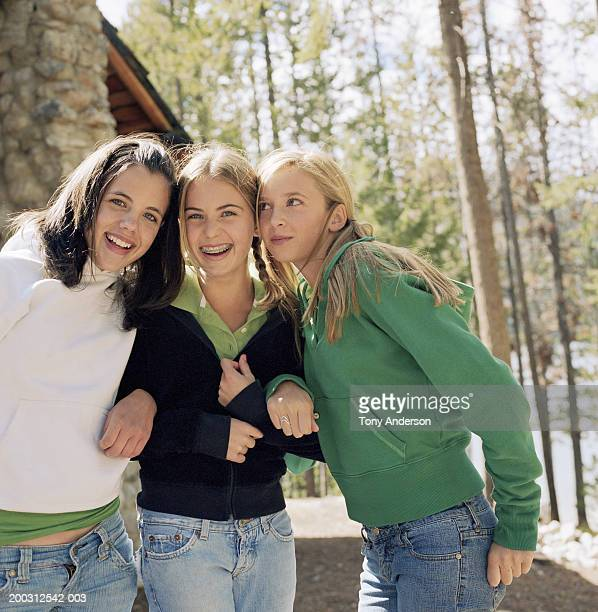 Three girls (10-14) putting heads together, laughing