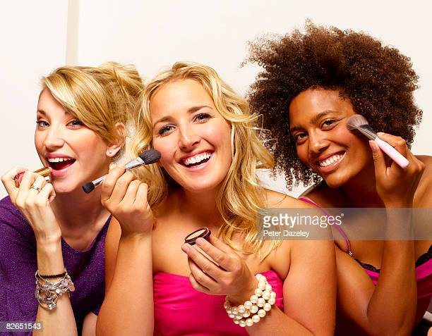 Three girls putting on make up in mirror