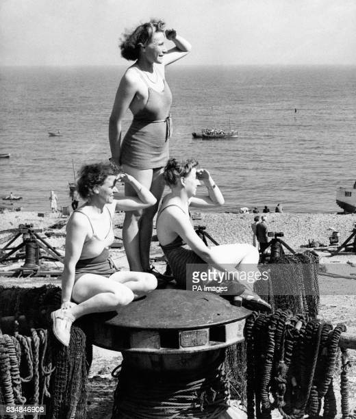 Three girls sit on a capstan to look out to sea at the seaside resort of Beer in Devon