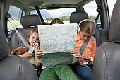 Three girls (6-8 years) sitting on rear seat of car on road trip