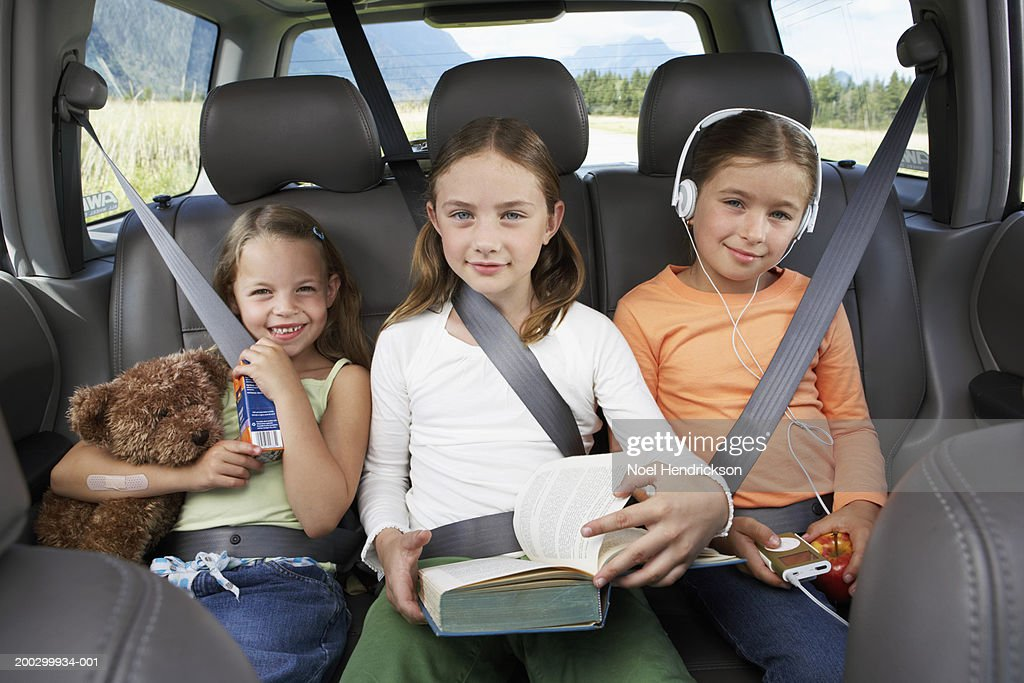Three girls (6-8 years) sitting on rear seat of car, smiling, portrait : Stock Photo