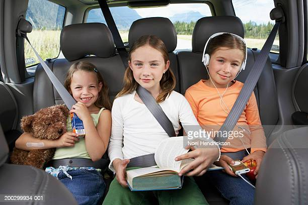Three girls (6-8 years) sitting on rear seat of car, smiling, portrait