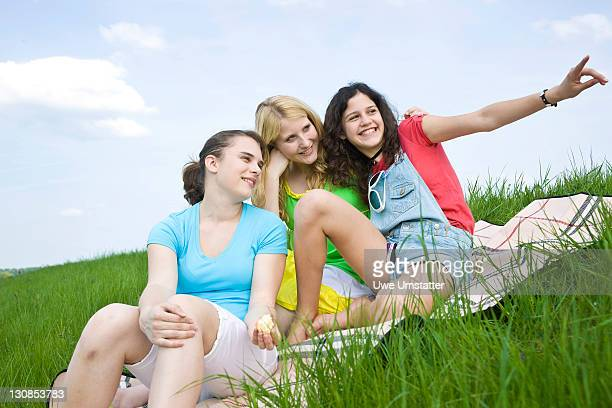 Three girls smiling while sitting on a blanket in the grass