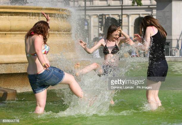 Three girls splash water in a fountain in Trafalgar Square in central London which has green water due to a build up of algae