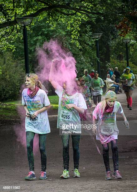 Three girls splashing themselves with pink color during the Color Run It is the world's largest series of 'fun runs' and for the second year in a row...