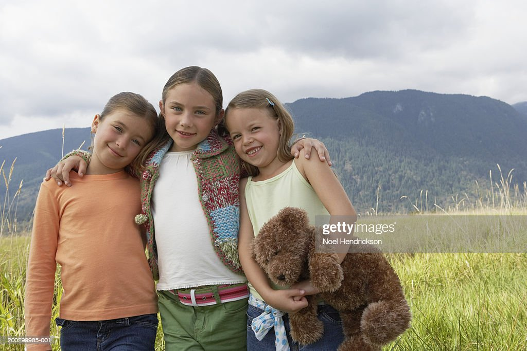 Three girls (6-8 years) standing arm in arm outdoors, smiling, portrait : Stock Photo