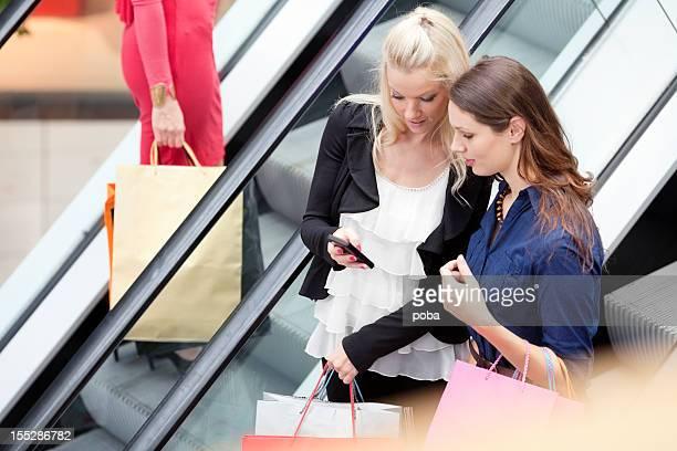 Drei Mädchen stehen auf der Rolltreppe tragen Einkaufstüten