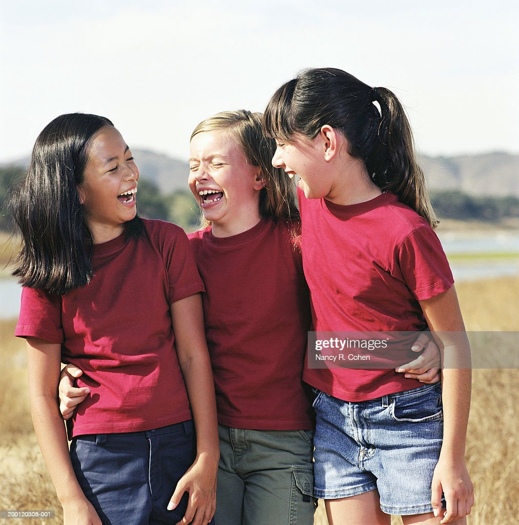 Three girls (8-10) standing with arms around each other, laughing : Stock Photo