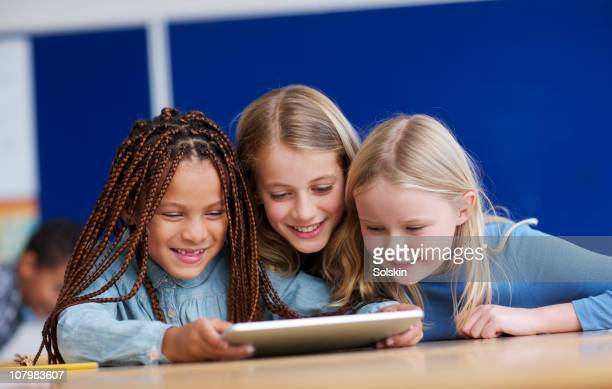 three girls using tablet computer in classroom