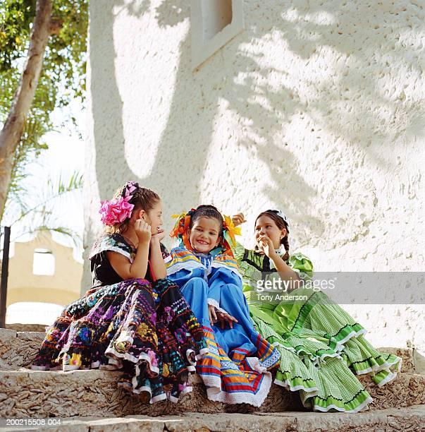 Three girls (5-9) wearing festival dresses, sitting on steps