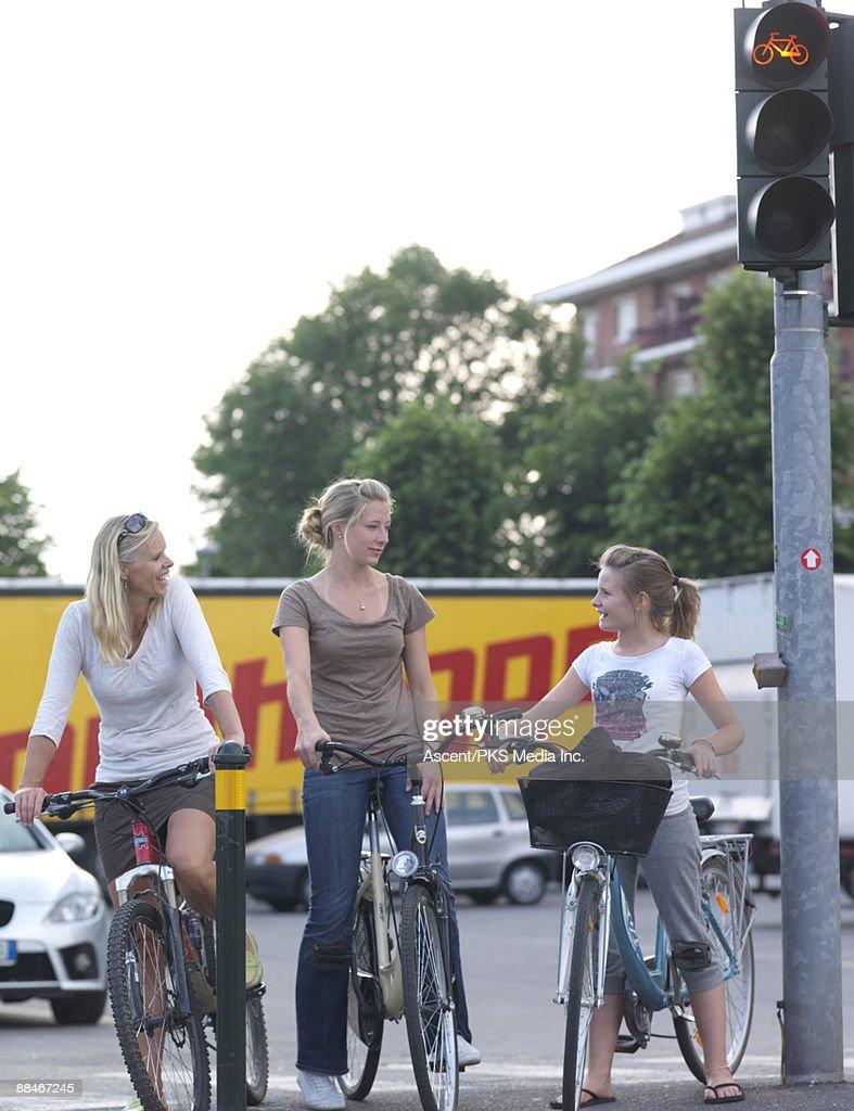 Three girls/women stop at bike crossing, on bikes : Stock Photo
