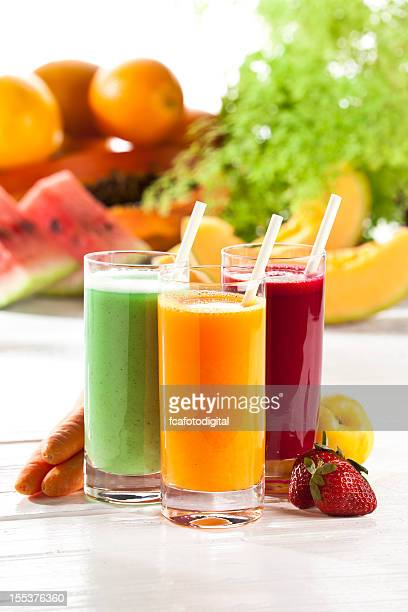 Three glasses of fruit juice with fruits in the background