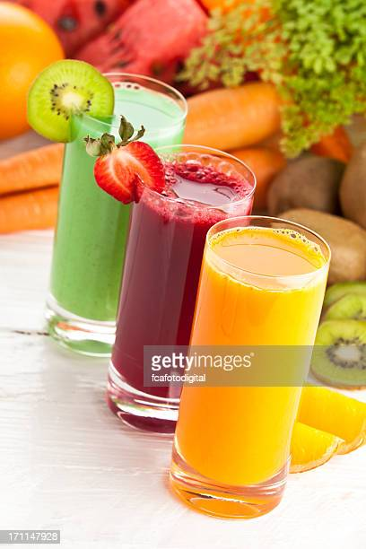 Three glasses of fruit juices and garnish on white table