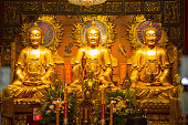 Golden Buddha statues in a row at a palace in Thailand.