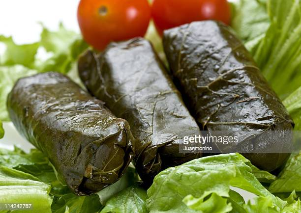 Three Greek dolmades resting on a lettuce leaf