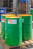 Three green barrels with label Poison standing on wooden pallets on a chemical plant