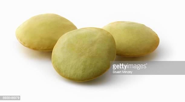 Three green lentils on white background