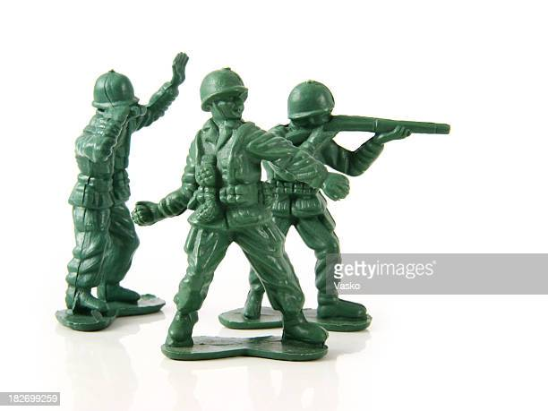 Three green toy soldiers dressed in their uniform