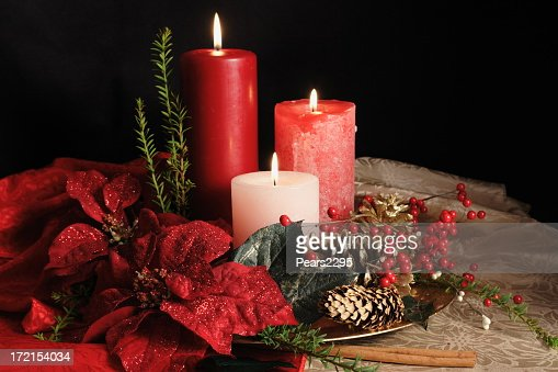 Three grouped Christmas candles standing among garlands