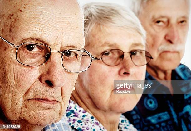 Three grumpy seniors, two men, one woman, frowning, disappointed