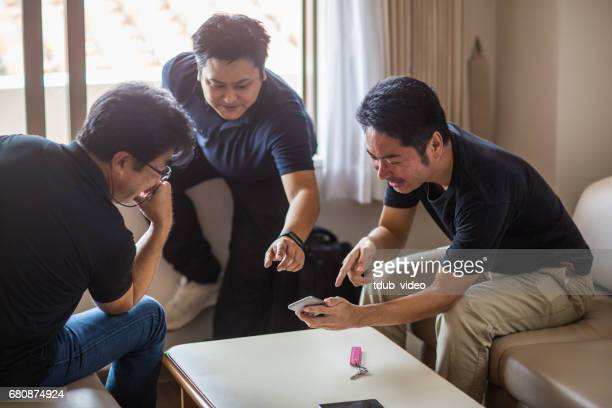 Three guys in a hotel room looking at a smart phone deciding what to do or where to go