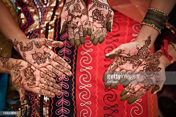 Three hands with henna