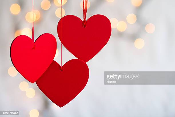 Three hanging red hearts on defocused light background.