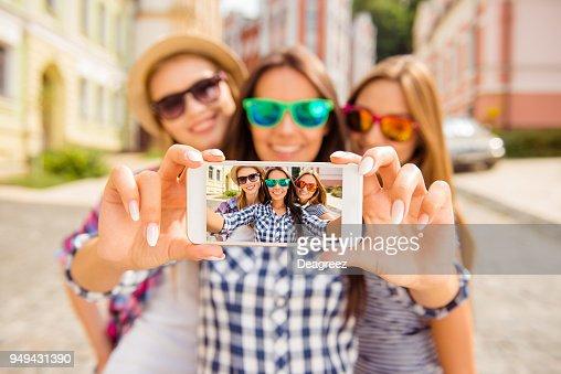 Three happy best girlfriends in glasses making selfie on smartphone : Stock Photo