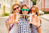 Three happy best girlfriends in glasses making selfie on smartphone
