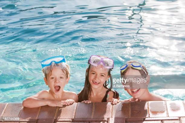 Trois heureux enfants nager dans la piscine