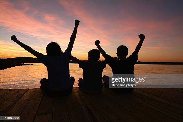 Three Happy Children with Arms Raised Silhouetted at Sunset