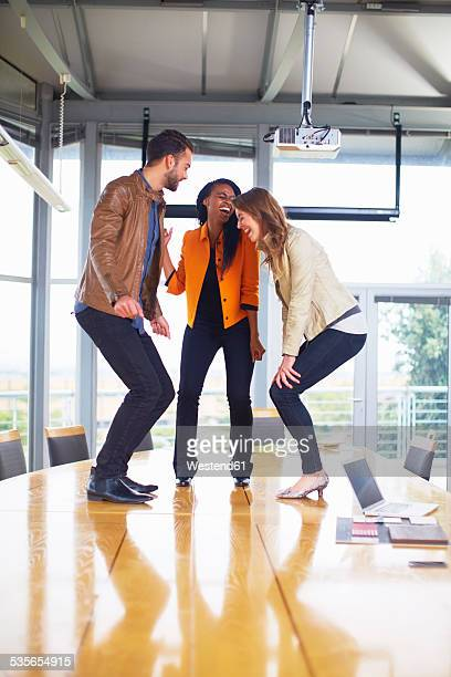 Three happy creative people dancing on a conference table