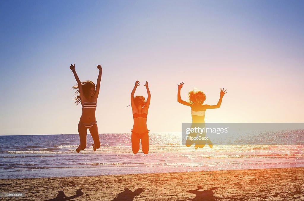Três felizes amigos saltar na praia de Verão : Foto de stock
