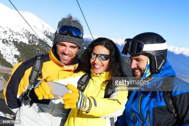 Drei glückliche Freunde nehmen Selfie in den Bergen