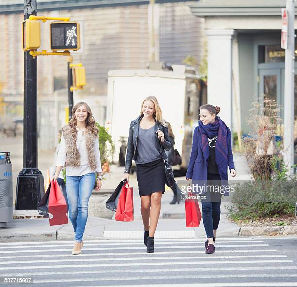 Three happy girlfriends walking with shopping bags in a city
