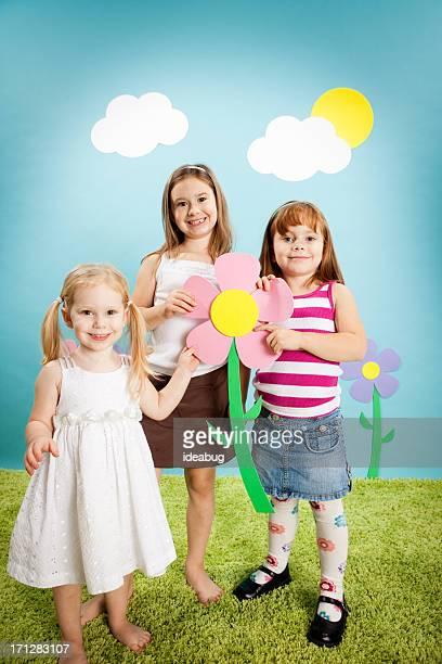 Three Happy Girls Holding Oversized Flower in Whimsical World