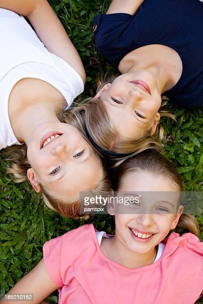 Three happy smiling little girls children lying on grass vertical