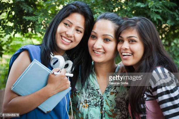 Three happy teenage girl students from different ethnicity in nature.
