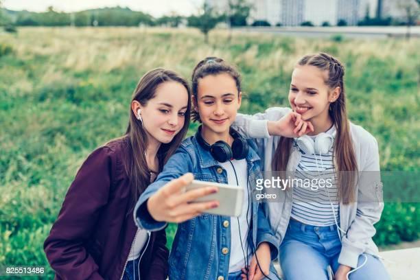 three happy teenage girls with smartphones outdoors