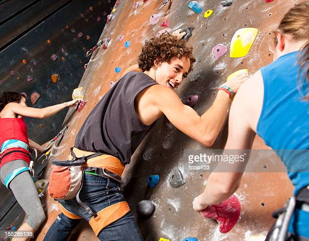 Three happy teenagers having fun at rock climbing wall