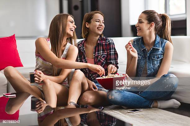 Three happy women eating popcorns at home and laughing.